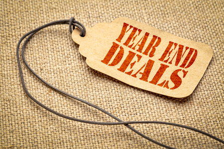 Year end deals sign - a paper price tag with a twine against burlap canvas