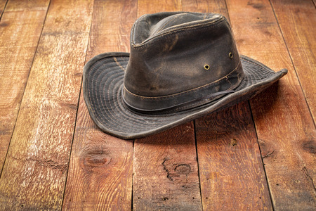 Weathered outback hat on rustic red barn wood Stock Photo