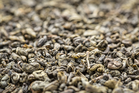Background texture of loose leaf Gunpowder  green tea, selective focus