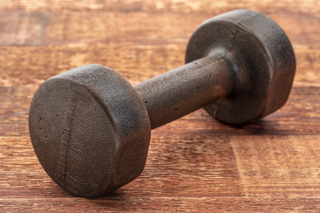 Vintage rusty iron dumbbell on grained wood background - fitness concept Stock Photo