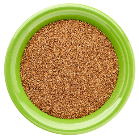 Gluten free brown teff grain in a round ceramic bowl isolated on white