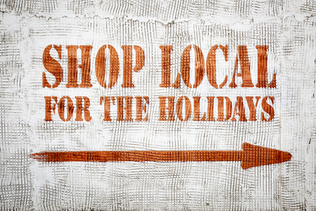 Shop local for the holidays - red graffiti sign with arrow on a white stucco wall Stock Photo