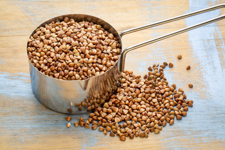 Gluten free buckwheat kasha in a measuring scoop (14 cup) against wood background