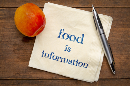 Food is information - handwriting on a napkin with a fresh apricot, diet and healthy lifestyle concept