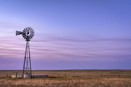 Windmill with a pump and cattle water tank in short grass prairie, Pawnee National Grassland in northern Colorado, summer dusk scenery Standard-Bild
