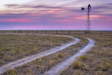 Windmill with a pump in short grass prairie, Pawnee National Grassland in Colorado near Grover Stock Photo