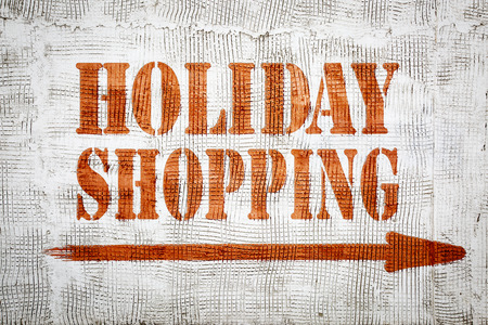 Holidays shopping - red graffiti sign with arrow on a white stucco wall