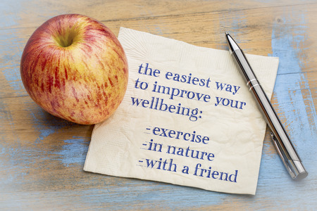 Advice on improving your well being - exercise, in nature, with a fiend - handwriting on napkin with a fresh apple Stock Photo