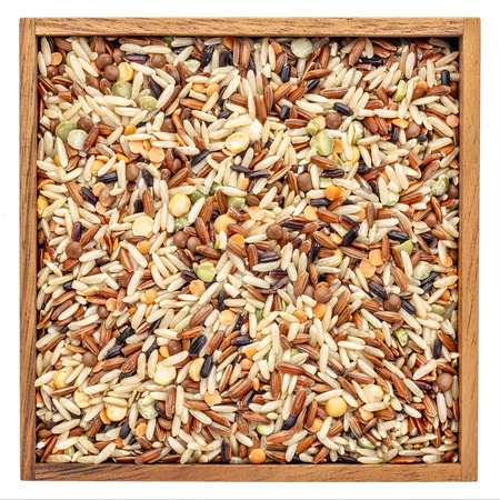 Pilaf mix with brown and black rice, Japonica rice, black eye, split green, yellow pea, lentils in a wooden box isolated on white