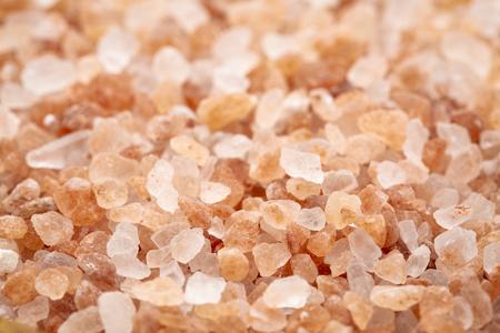 Background of Himalayan salt - pink and orange coarse crystals, selective focus