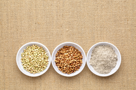 Gluten free buckwheat groats, roasted kasha and flour - a row of small ceramic bowls against burlap canvas
