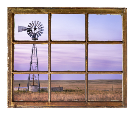 Windmill with a pump and cattle water tank in short grass prairie at dusk as seen from a vintage cabin window