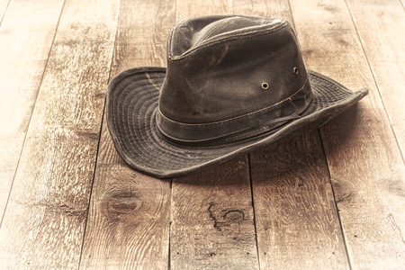 Weathered outback hat on rustic red barn wood, sepia toned image Stock Photo