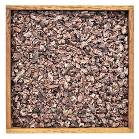 background of raw cacao nibs in an isolated wooden box