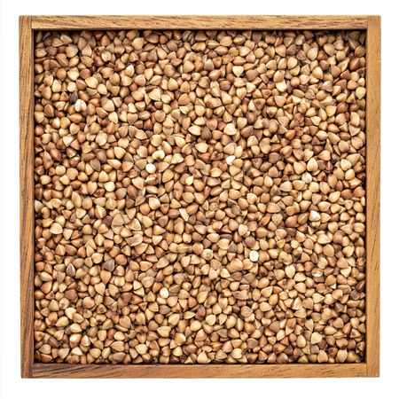 buckwheat kasha in an isolated wooden box, top view Stock Photo