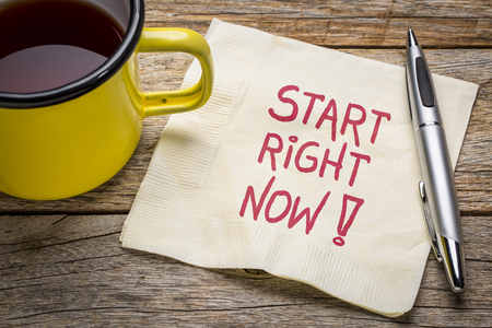 Start right now - motivational note on napkin with a cup of tea