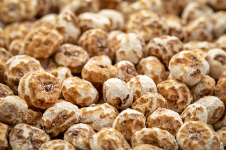 organic peeled tiger nuts, a rich source of resistant starch, top view background with selective focus