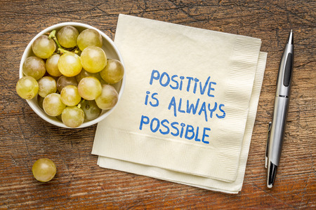Positive is always possible - inspirational handwriting on a napkin with fresh grapes