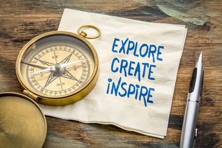 explore, create, inspire concept - inspiraitonal handwriting on a napkin with an antique brass compass Stock Photo