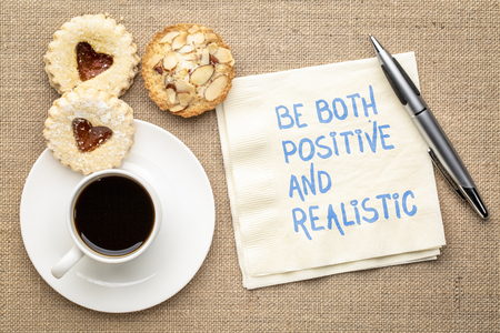 Be both positive and realistic - inspiraitonal handwriting on a napkin with a cup of coffee and cookies
