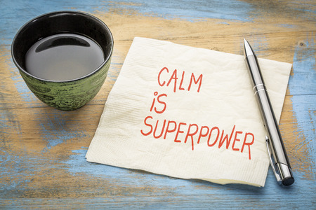 Calm is superpower note - inspirational handwriting on a napkin with a cup of tea