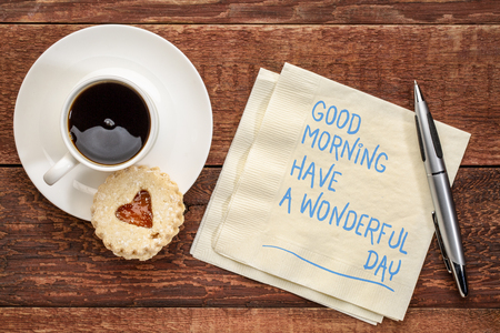 Good Morning, have a wonderful day - handwriting on a napkin with a cup of coffee and cookie