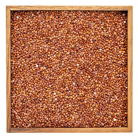 gluten free red quinoa grain in a square wooden box isolated on white