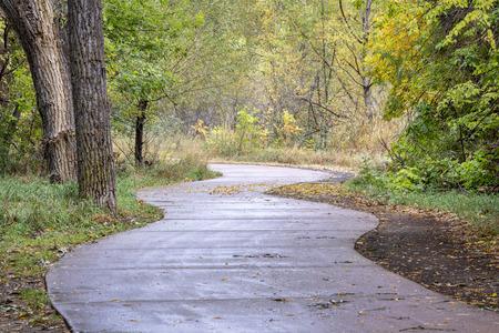 Ventoso sendero para bicicletas a lo largo del río Poudre en Fort Collins, Colorado - día lluvioso con colores de otoño