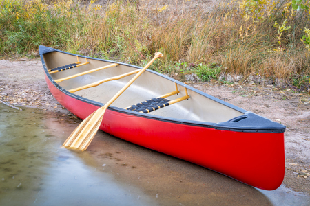 red tandem canoe with a wooden paddle on a lake shore
