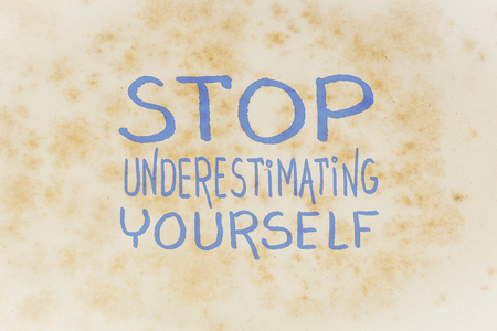 Stop underestimating yourself - inspirational handwriting on an old yellowed paper Standard-Bild