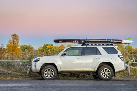 Fort Collins, CO, USA - October 12 ,2018: After paddling - Toyota 4Runner SUV (2016 trail model) with an expedition stand up paddleboard by Starboard at dusk on the lake shore.