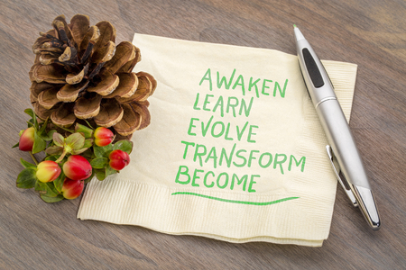 awaken, learn, evolve, transform and become - inspirational words - handwriting on a napkin with a pine cone