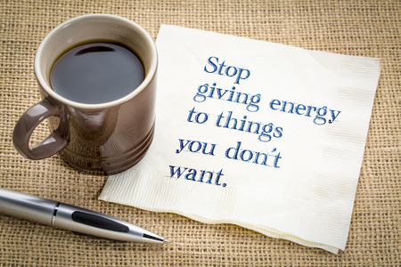 Stop giving energy to thing you do not want - handwriting on a napkin with a cup of coffee