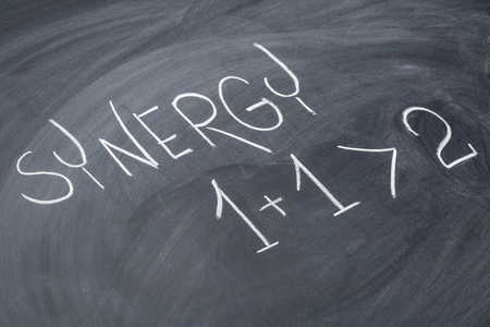 synergy concept in white chalk handwriting on a blackboard Stock Photo