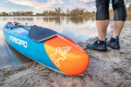 Fort Collins, CO, USA - October 17, 2018: Racing stand up paddleboard on a calm lake in fall scenery of northern Colorado  - 2018 model of All Star SUP by Starboard.