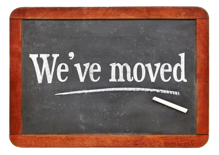 We have moved sign - white chalk text on a vintage slate blackboard Stock Photo