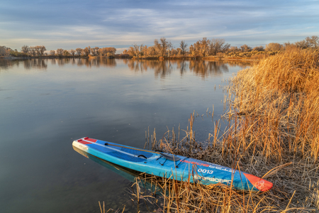 Fort Collins, CO, USA - October 28, 2018: Racing stand up paddleabord by Starboard at a shore of calm lake at sunset.
