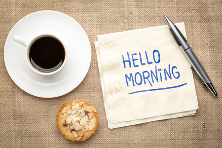 Hello morning - handwriting on a napkin with a cup of coffee