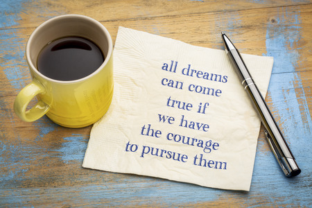 All dreams can come true if you have courage to pursue them - handwriting on a napkin with a cup of espresso coffee 版權商用圖片