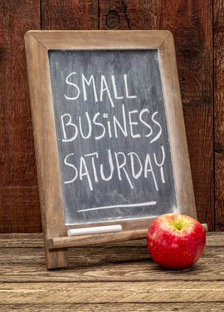 Small Business Saturday sign - white chalk handwriting on a blackboard agains rustic barn wood - holiday shopping concept Stock fotó