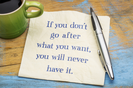 If you do not go after what you want, you will never have it - handwriting on a napkin with a cup of espresso coffee