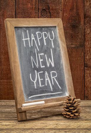 happy new year greetings - white chalk text on a blackboard against barn wood