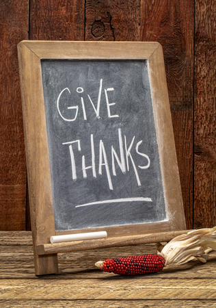 give thanks - Thanksgiving concept - rustic blackboard sign with a decorative corn against barn wood