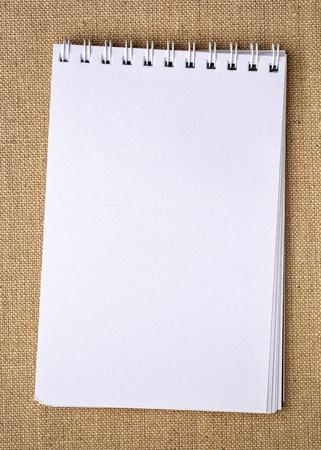 blank spiral sketchbook against burlap canvas background Stock Photo