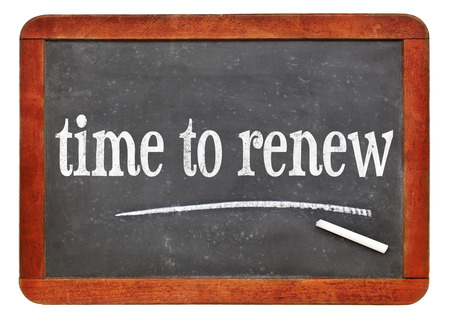 time to renew sign - white chalk text on a vintage slate blackboard