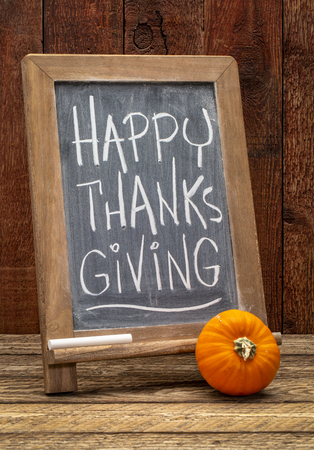 Happy Thanksgiving greeting card - white chalk handwriting on a blackboard with a pumpkin gourd agains barn wood Stock Photo