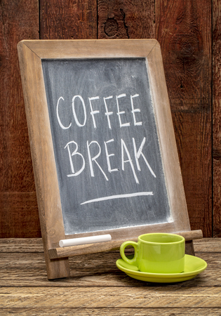 coffee break sign - white chalk handwriting on a blackboard with a cup of coffee