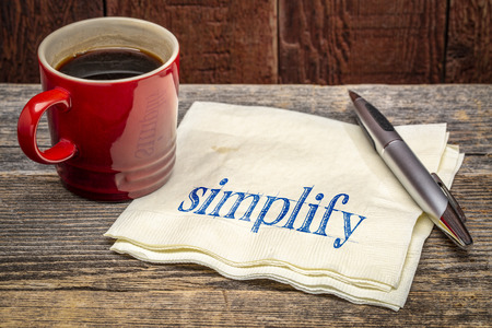 simplify advice -  handwriting on a napkin wioth a cup of coffee against rustic wood