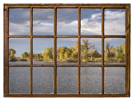 lake in Colorado with a dramatic sky and fall colors as seen from a vintage window