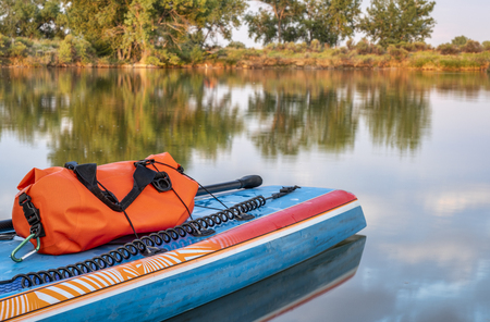 Stand up paddleboard with a paddle, safety leash and waterproof duffel on a shore of calm lake in northern Colorado, summer scenery Stock Photo